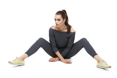 Girl in overalls with legs spread. Beautiful young woman in grey overalls and yellow sport shoes with legs spread. Isolated over white background. Copy space Royalty Free Stock Photos