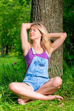 Girl in overalls relaxes outdoors Stock Photography