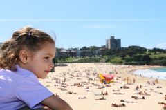 Girl overlooking crowded summer beach. On summer day Stock Image