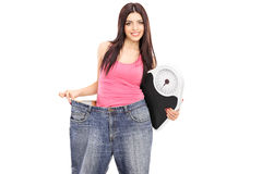 Girl in oversized jeans holding a weight scale Stock Photos