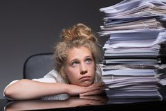 Girl overwhelmed by paperwork. Portrait of depressed girl overhelmed by paperwork Royalty Free Stock Photography