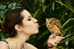 Girl with an owl. Pretty young girl kissing the owl bird in the national park, Pattaya, Thailand Royalty Free Stock Photos