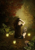 Girl and Owl. The young girl holding up hair up, looking over his shoulder, sitting on the grass with owl on her leg, illuminated by the light of lanterns in the Royalty Free Stock Photography