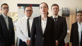 The girl owner of the business proudly stands in a jacket, behind her are her employees stock video