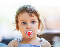 Girl with a pacifier. Little girl with a pacifier being contemplative royalty free stock photo
