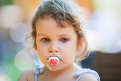 Girl with a pacifier. Little girl thoughtful holding a pacifier in her mouth stock image