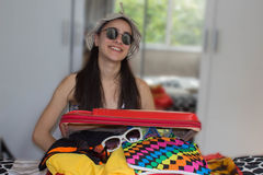 Girl packing bag for travel, closing hardly overfilled luggage bag Stock Photo