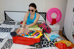 Girl packing bag for travel. Woman with suitcase sitting on bed in hotel Stock Photos