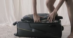 Girl packing and closes her suitcase. Preparing bag for travel. Young woman packing and standing her bare knees on overfilled suitcase and closes a zipper on it stock footage