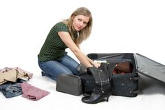 Girl is packing clothes. Separate on white Royalty Free Stock Photo