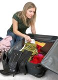 Girl is packing clothes. I bag, separate on white Royalty Free Stock Photo