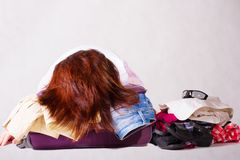 The girl packing crammed suitcase Stock Photography
