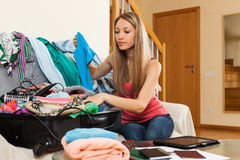Girl packing luggage. Attractive girl sitting on sofa and packing luggage Stock Photography