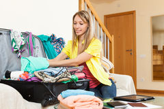 Girl packing luggage. Smiling attractive girl sitting on sofa and packing luggage Stock Images