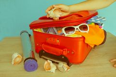 Girl packing suitcase at home. Open suitcase packed for travelling, close up royalty free stock photo