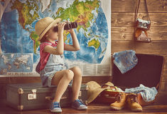 Girl packs bags. Happy baby girl getting ready for the journey. Girl packs her bags and playing with binoculars Royalty Free Stock Photos