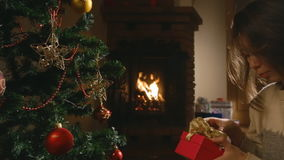 Girl packs a a gift sitting around the Christmas tree. Christmas presents. Girl packs a a gift sitting around the Christmas tree stock video footage