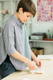 Girl packs a gift on a wooden table stock photos