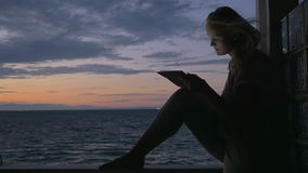 Girl with pad on outdoor terrace in the evening. Slow motion of a young woman using tablet computer sitting on the wooden balcony rail of a seaside house. Light stock video