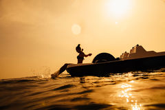 Girl on paddle boat catamaran with sunlight and splash Stock Photography