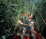 Girl with a paddle in a boat swam into a reed stock photos
