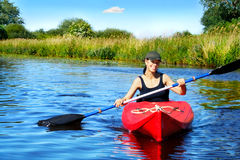 Girl with paddle and kayak 4. Girl with paddle and kayak on a small river in rural landscape Royalty Free Stock Images