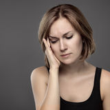 Girl with a painful head. On a grey background Royalty Free Stock Photos