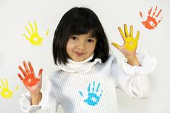Girl and paint. Girl and her hand print on the wall Royalty Free Stock Image