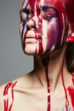 Girl with paint on her Face. liquid paint flow royalty free stock image