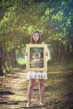 Girl with a paint of herself in the woods Stock Photos