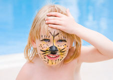 Girl with paint on his face. In the pool Stock Image