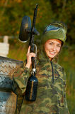 Girl paintball player. Happy paintball sport player girl in protective camouflage uniform and mask with marker gun outdoors Royalty Free Stock Image