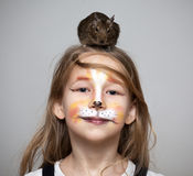 Girl painted as a cat with grey mouse on the head. Little girl painted as a cat makeup with grey mouse on the head Stock Photography