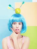Girl with Painted Blue Hairs and Apple on Head Stock Photo