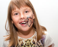 Girl with painted face. Female child with painted fish on her face - smile Royalty Free Stock Photos