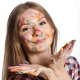 Girl with painted face and hands in colorful paints Royalty Free Stock Photography
