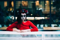 A man with a painted face of a skeleton, a dead zombie, in the city during the day. day of all souls, day of the dead, halloween, stock images