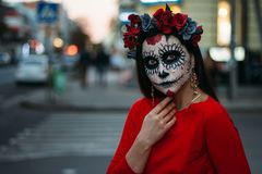 A man with a painted face of a skeleton, a dead zombie, in the city during the day. day of all souls, day of the dead, halloween, stock photos