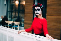 A girl with a painted face of a skeleton, a dead zombie, in the city during the day. day of all souls, day of the dead, halloween, royalty free stock photo