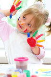 Girl with painted hands. Cute little girl with painted hands indoors royalty free stock photo