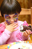 Girl painted for holiday eats cake Royalty Free Stock Photos