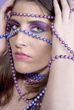 The girl with painted pearls. Attractive young woman with painted pearls on hands and over face wearing matching makeup Stock Images
