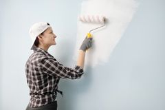 Girl painter, designer and worker paints a roller and brush the wall. Smiling, working with pleasure, close-up. stock image