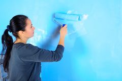 Girl painter engaged. In painting the walls, repairing the house royalty free stock image