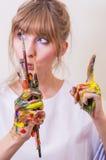 Girl painter holding paintbrushes royalty free stock photos