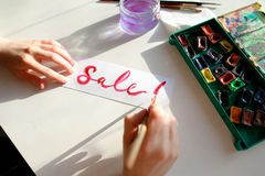 Girl painter writes with brush and paints inscription on sheet, Royalty Free Stock Photos