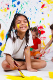 Girl painting. A cheerful African American girl painting Royalty Free Stock Images