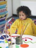 Girl Painting In Art Class. Cute little girl painting in art class stock photography