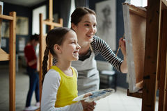 Girl Painting in Art Class. Portrait of happy little girl enjoying painting class in art studio, with young teacher helping her stock photo