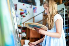 Girl Painting in Art Class. Side view portrait of pretty teenage girl painting picture on easel in art class, holding color palette stock photography
